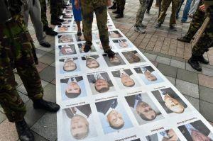 Des militants de l'EuroMaidan piétinent un parterre de photos de députés du Parti des Régions et du parti communiste, le 17 juin 2014.  Photo: AFP