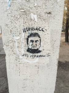 """Donbass is Ukraine"", a graffiti claims on a pillar of Lougansk university. The graffiti displays the face of former President Viktor Yanukovych. A Nazi cross was added to the graffiti."