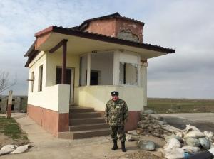 L'officier Skarvinko devant un bâtiment laissé à l'abandon, dans le no man's land, le 19/03/2015.