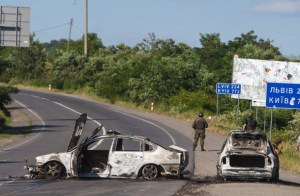 Servicemen stand next to burnt cars in Mukacheve, southwestern Ukraine on July 11, 2015 where at least two people were killed and several more injured in fighting that erupted on July 11 between police and heavily armed members of ultranationalist Pravy Sektor movement. AFP PHOTO/ ALEXANDER  ZOBIN